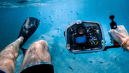 man with camera under the sea